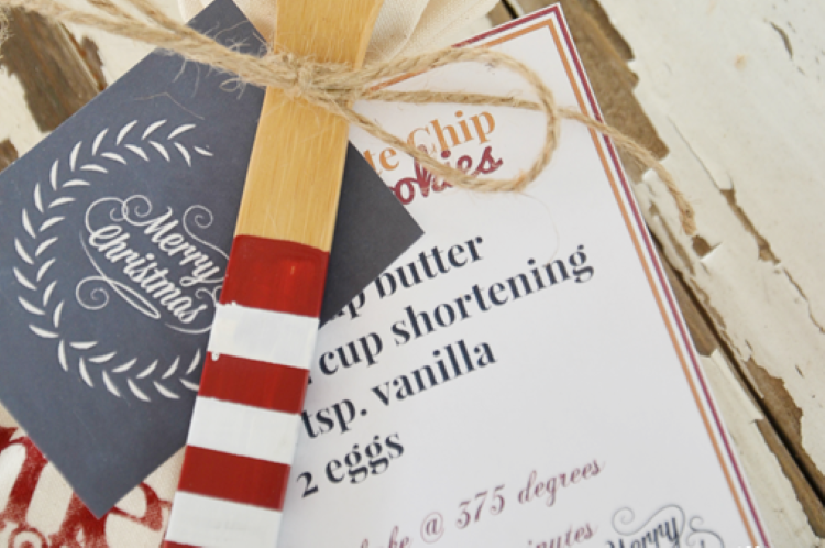 A Christmas gift tag and chocolate chip cookie recipe attached to a wooden spoon | The Dating Divas