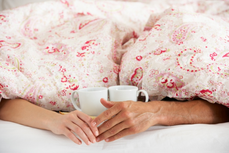 Couple holding hands and exchanging anniversary gifts in bed | The Dating Divas