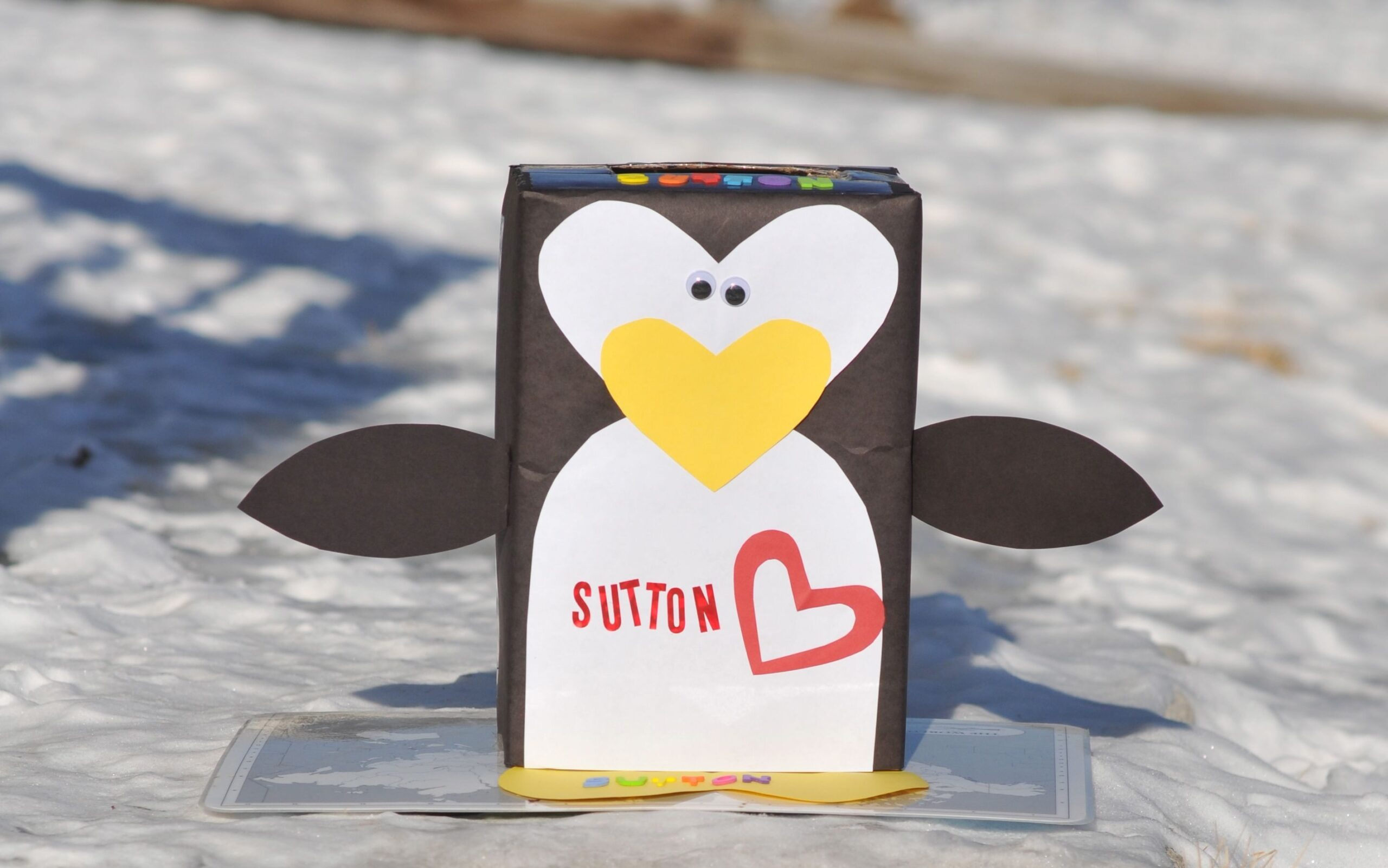 Adorable penguin with a yellow heart nose valentine box idea | The Dating Divas