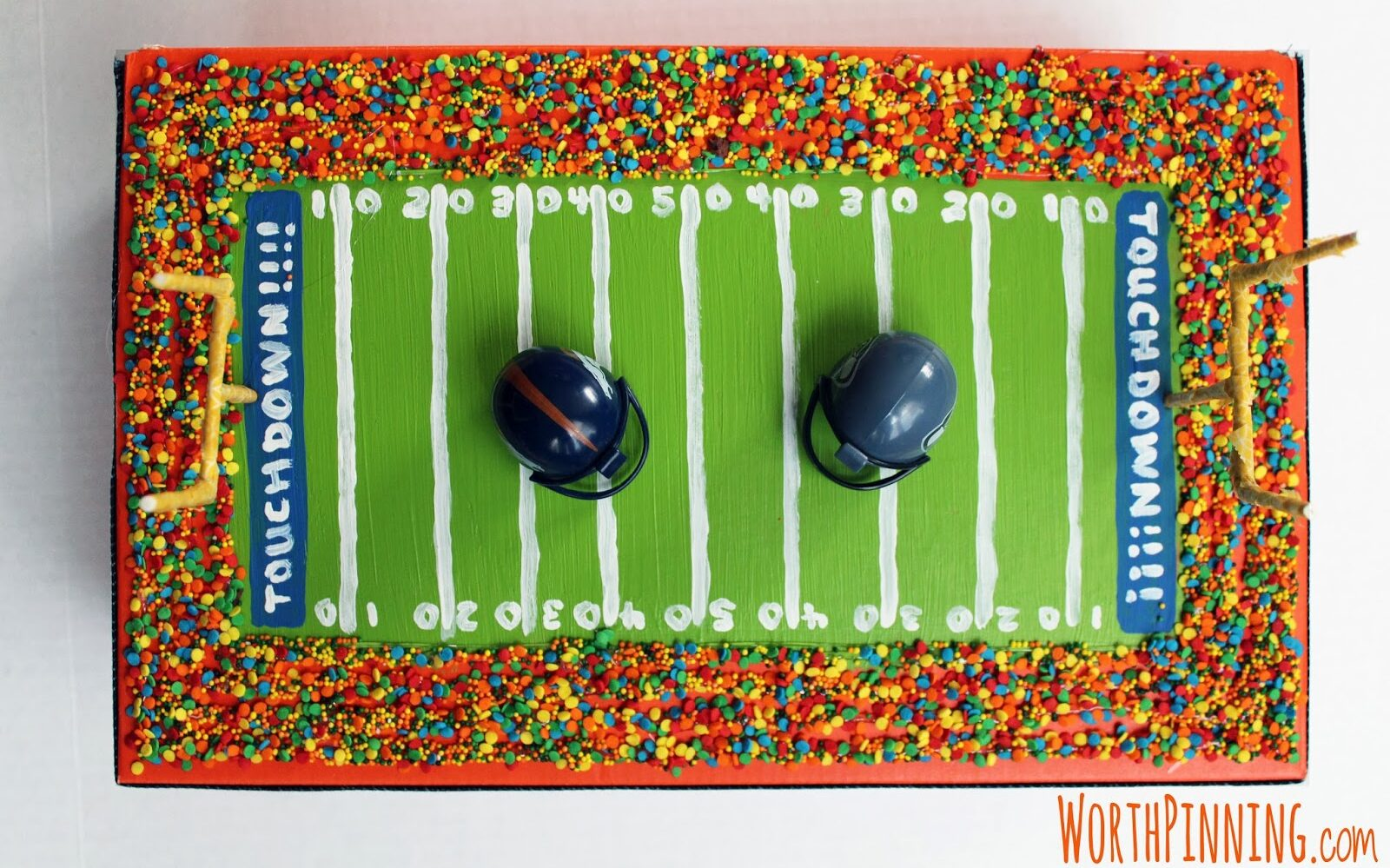 Bright football field themed box with football helmets on top for Valentine's Day | The Dating Divas