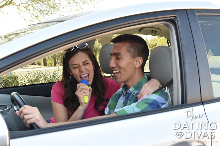 A couple in the car doing a car sing along date. | The Dating Divas