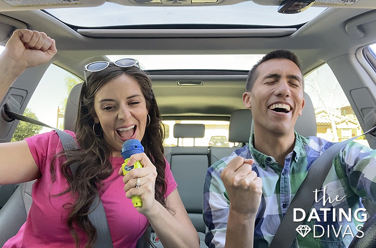 Couple in a car singing along to fun road trip songs. | The Dating Divas