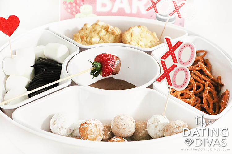Couple enjoying their chocolate fondue date by dipping strawberries into chocolate fondue | The Dating Divas