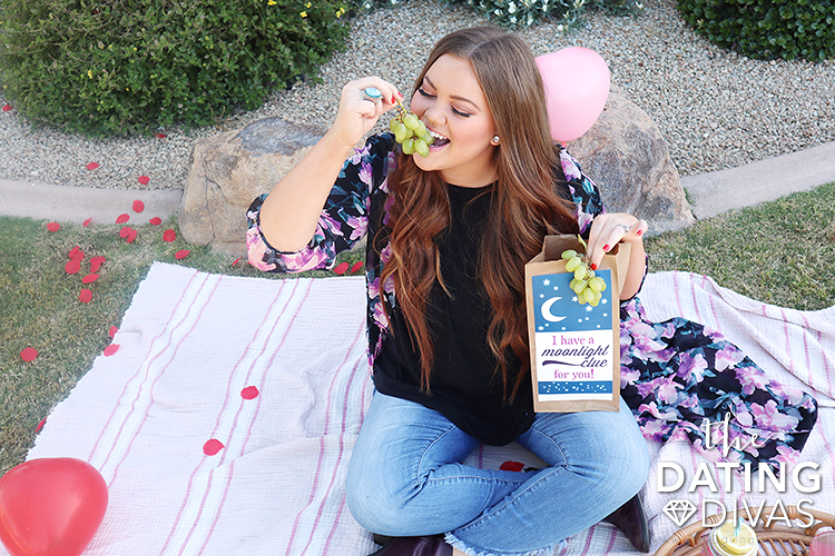 Girl on a picnic eating grapes | The Dating Divas