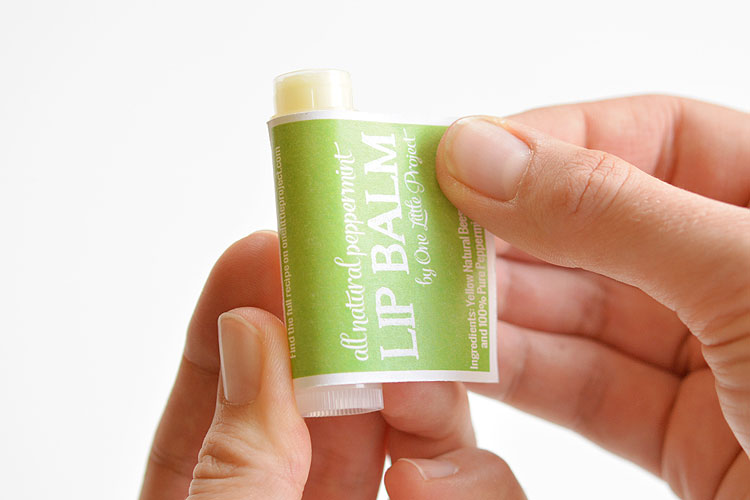 Homemade lip balm getting wrapped with a label | The Dating Divas