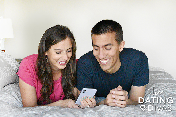 Couple looking at a phone and discussing a question from a conversation starter app. | The Dating Divas