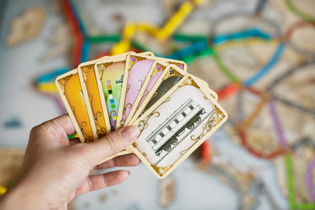 Women holding Ticket To Ride European version cards while playing | The Dating Divas