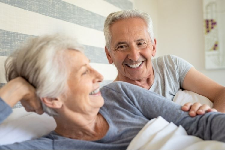 Happy older couple with Alzheimer's laying in bed   The Dating Divas