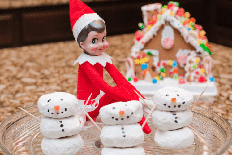 Elf on the shelf sits by snowmen made out of mini donuts   The Dating Divas