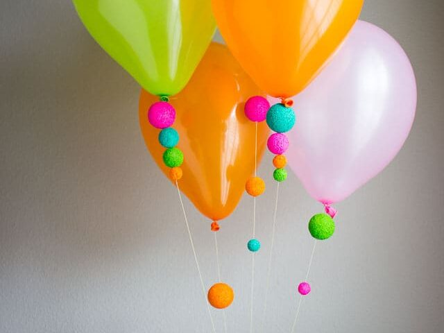 Neon-painted Styrofoam balls are added to the strings of balloons for a birthday party decoration | The Dating Divas