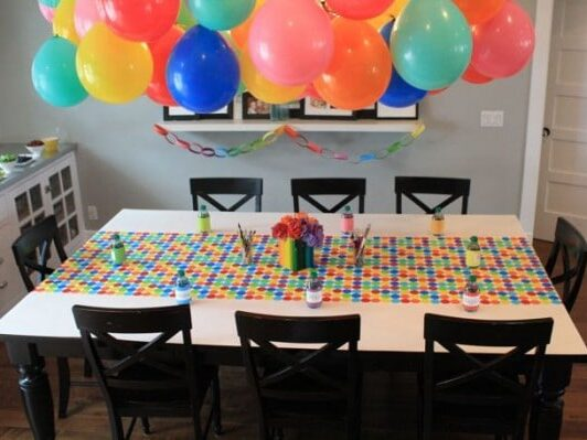 Chandelier created with balloons hangs over the dining area for birthday party decorations | The Dating Divas