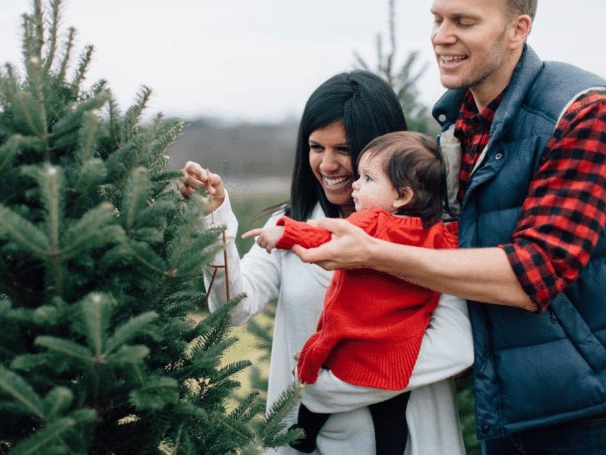 A Christmas photo that shows a young family at a tree farm | The Dating Divas