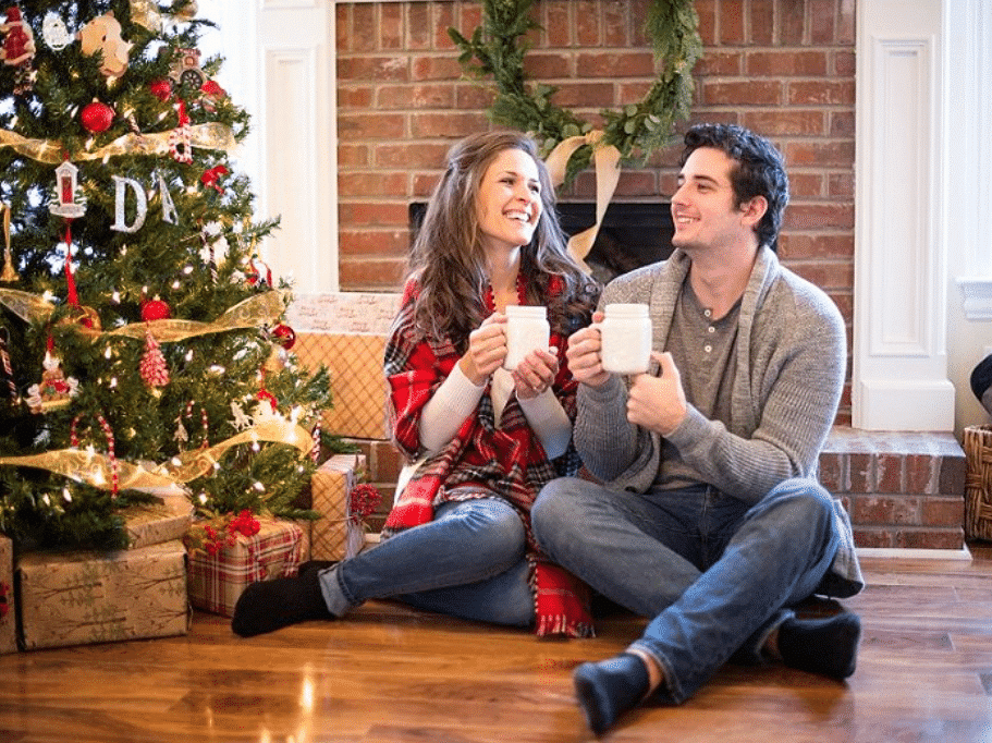 Christmas card ideas that show a young couple drinking cocoa by the tree | The Dating Divas