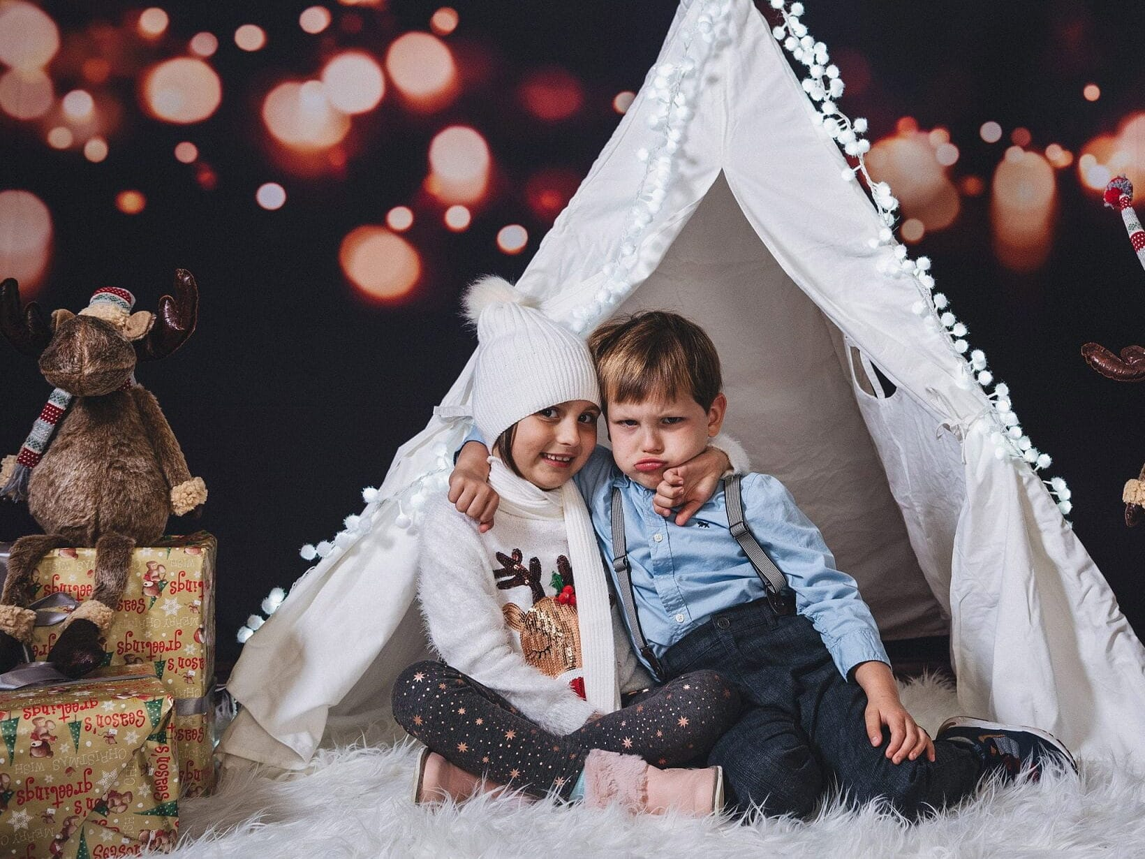 Family Christmas pictures that show two young children sitting in front of a tent | The Dating Divas
