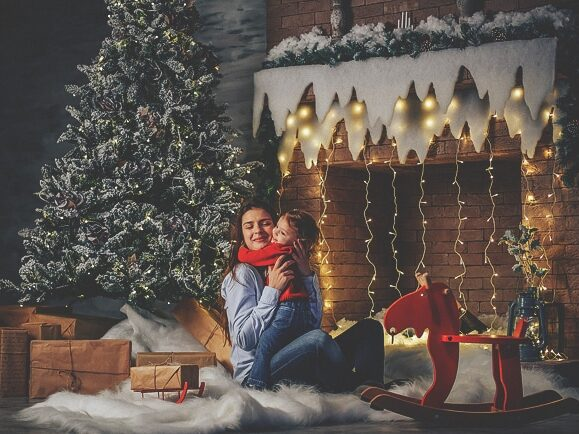 Family Christmas card ideas showing a mother and child in front of the fireplace | The Dating Divas