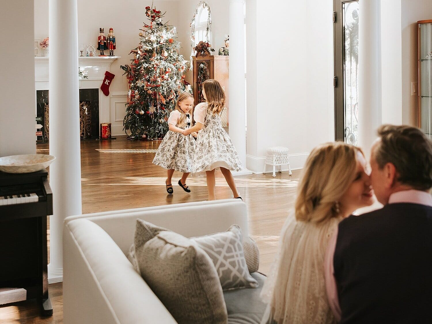 Family Christmas cards ideas showing sisters dancing in front of the tree | The Dating Divas
