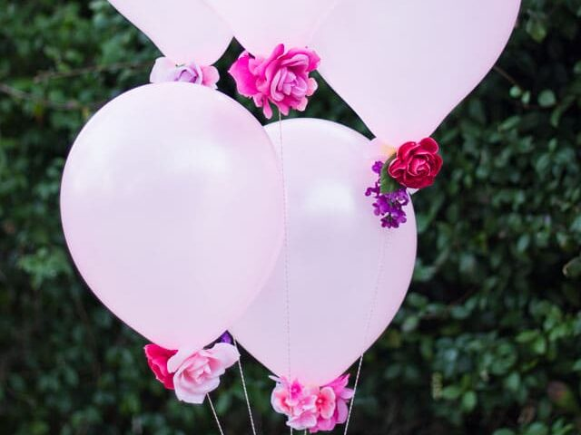 Add flowers to the bottom of balloons for a whimsical birthday decoration idea | The Dating Divas