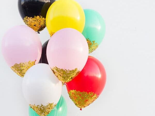Apply glitter to the bottom of balloons to make sparkly birthday party decorations | The Dating Divas
