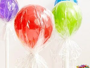 Balloons wrapped in cellophane to make lollipop balloons at a kid's birthday party | The Dating Divas