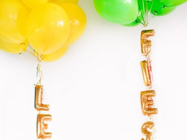 Mini lettered balloons attached to the strings of balloon clusters at a birthday party | The Dating Divas