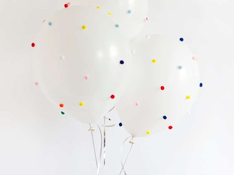 Add colorful pom-poms to balloons for birthday decoration ideas | The Dating Divas