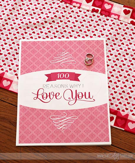 pink cover of the 100 reasons why I love you book on heart table cloth